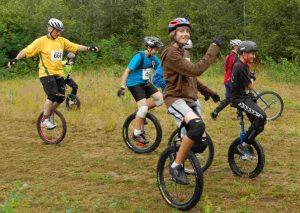 cette image montre 5 personnes qui font de monocycle