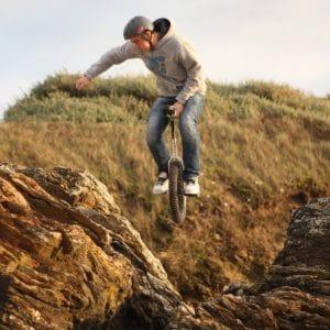 cette image montre un homme sur un monocycle dans la nature